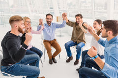 Therapy of sincerity between people. Happy group is sitting and holding hands. They also raising them up with funny smiles stock photo
