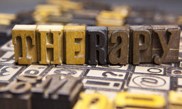 Therapy in wooden typeset. The word Therapy  surrounded by random typeset Stock Photography