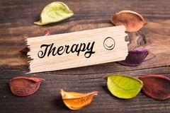 Therapy word in card. Therapy word in wooden card with dried flower on wood stock photo