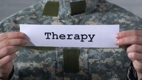 Therapy written on paper in hands of male soldier, help to war veterans