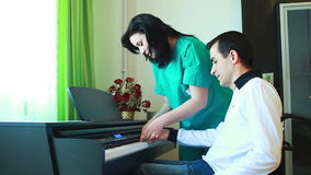 Therapy for young man in wheelchair using piano Royalty Free Stock Image