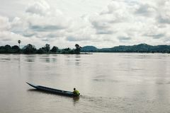 theravada buddhist monk driving a motor canoe on the mekong river stock photography