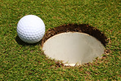 Almost There. A golf ball on the edge of a hole Stock Images
