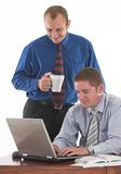 Almost there. Two businessman working on the desk over white Royalty Free Stock Photography