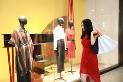 Pretty Asian Chinese modern fashionable woman girl smile shopping card and bag in a mall store casual buyer walk by window. There is a Asian Chinese modern woman royalty free stock image
