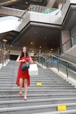 Pretty Asian Chinese modern fashionable woman girl smile shopping card bag in a mall store casual buyer walk on stairs adult. There is a Asian Chinese modern stock photos