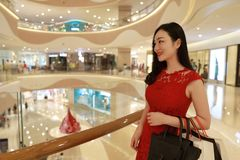 Happy Asian Chinese fashionable woman shopping bags in a mall store casual buyer smile laugh consumption on sale promotion VIP. There is a Asian Chinese modern royalty free stock images