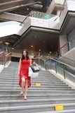 Pretty Asian Chinese modern fashionable woman girl smile shopping card bag in a mall store casual buyer walk on stairs adult stock images