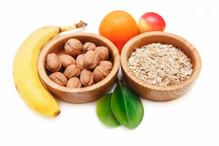 There are Banana,Apзle,Orange with Walnuts in the Wooden Plate and Rolled Oats,with Green Leaves,Healthy Fresh Organic Food Stock Photo