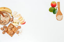 There are Banana,Apple,Orange with Walnuts in the Wooden Plate and Rolled Oats,Wooden Spoon,Trivet,with Green Leaves,Healthy Fresh Royalty Free Stock Image