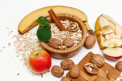 There are Banana,Apple,Orange with Walnuts in the Wooden Plate and Rolled Oats,Wooden Spoon,Trivet,with Green Leaves,Healthy Fresh Stock Photos