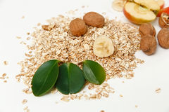 There are Banana,Apple with Walnuts and Rolled Oats,Wooden Trivet,with Green Leaves,Healthy Fresh Organic Food on the White Backgr Stock Photography