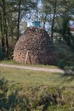 There is a beehive on a pile of firewood. There is a road ahead of the firewood. Near the road grows green grass and trees Royalty Free Stock Photos
