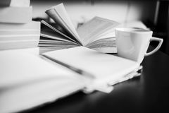 There are coffee, books, notebook and pen. Note-taking. Black and white photo Royalty Free Stock Photography
