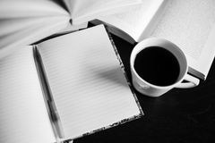 There are coffee, books, notebook and pen. Note-taking. Black and white photo Stock Images