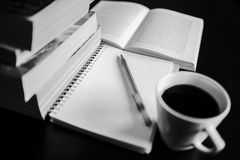 There are coffee, books, notebook and pen. Note-taking. Black and white photo Royalty Free Stock Photo