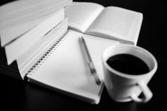 There are coffee, books, notebook and pen. Note-taking. Black and white photo Stock Photo