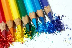 Colored pencils and their powder. There are colored pencils sharpened on white paper and their powder stock photography