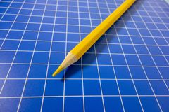 There is a coloured pencil on the checkerboard. There is a coloured pencil on the blue checkboard royalty free stock photography