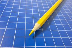 There is a coloured pencil on the checkerboard. There is a coloured pencil on the blue checkboard stock image