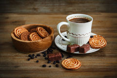 There are Cookies,Candy,Chocolate Peas,Poppy;Porcelain Saucer and Cap with Coffe,Tasty Sweet Food on the Wooden Background,Toned Stock Image