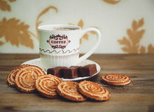 There are Cookies,Chocolate Candy, Porcelain Saucer and Cap with Coffe,Tasty Sweet Food on the Wooden Background,Toned Royalty Free Stock Photos