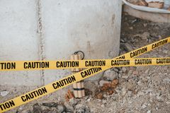 There could be catastrophic consequences. Dangerous explosive lying on the ground. Yellow caution tape in front