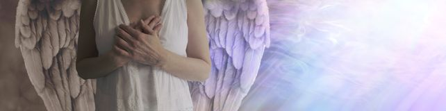 There is dark and light in all. Angel showing torso in white robes with hands held over heart with left side shaded in darkness and right side lit by a stream of Royalty Free Stock Photography