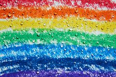There are drops of water dripping over a rainbow with crayons. Water droplets are scattered on a rainbow drawn with colored crayons royalty free stock photo