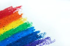 There are drops of water dripping over a rainbow with crayons. Water droplets are scattered on the rainbow drawn with crayon, and the right of the screen is royalty free stock images