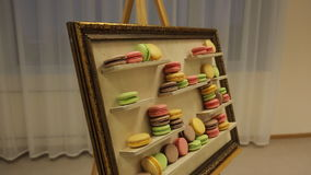 There is easel with macaroons served as picture of art. stock video footage