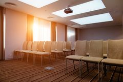 There is an empty big meeting hall with rows of cream chairs. Modern brown curtains and tulle. briefings in room Stock Photo