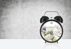 There is EURO bills inside the alarm clock which is on the table. The concept of 'time is money' and a time management. Royalty Free Stock Photos