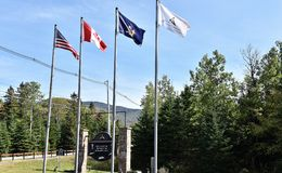 Lake placid olympic sport complex entrance flags. There are flags of USA, Canada, New York state and Olympic regional development authority on the entrance of royalty free stock images