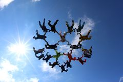 Skydivers are flying together in the blue sky. royalty free stock image