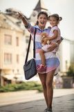 There is a fun for us. Mother showing something to her daughter on city street. Close up. Copy space stock image