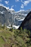 Spring view of the mountain cirque de Gavarnie. There are a green slope with a hiking trail against the stone walls with the waterfall and the glaciers in the Royalty Free Stock Photos