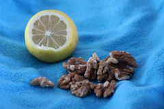There is a Lemon and Walnut on the Blue Background on the photo. There is a half of Lemon and walnut on the blue background on this photo Royalty Free Stock Photo