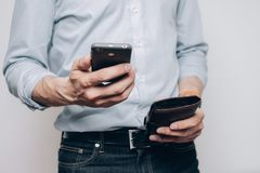 The hands with a phone and wallet. There the hands with a black phone and brown wallet close-up royalty free stock images