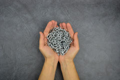 There are hands holding a silver metal chain on the grey background Stock Image
