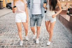 There are human`s legs on picture. Thee are one guy an two girls besides him. Blonde girl is holding cup of coffee. Brunette girl is posing. They are walking royalty free stock image