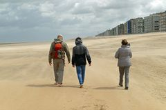 People walking on the beach during a hurricane with strong sand drifts stock photography