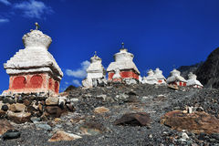 There is a large many ancient Buddhist stupa on the steep slope of the mountain under a bright blue sky: the stupas are set on a s. Many ancient Buddhist stupa Stock Images