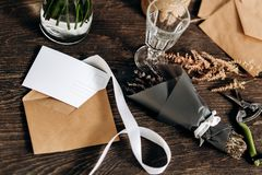 There are little bouquet of flowers, wineglass, postcard, envelopes and white ribbon on the wooden table stock photo