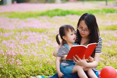 Happy little cute baby girl smile and read book with mother, mom tells story to his daughter in a summer park happy family stock photo