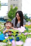 Happy little cute baby girl smile and laugh read book with mother, mom tells story to his daughter in a summer park happy family stock photo