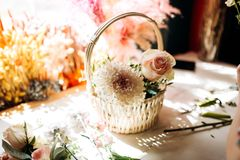 There is a little white basket with white peony and rose on the wooden table in the flower shop stock photos