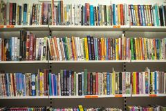 Books in library. There are many colorful books on a shelf in a library Stock Images
