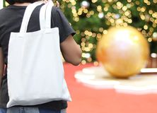 Model hold blank white fabric tote bag for save environment on street fashion with white t-shirt