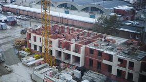There is a multi-apartment building made of bricks. A construction crane loads brick on the house, builders in stock video footage